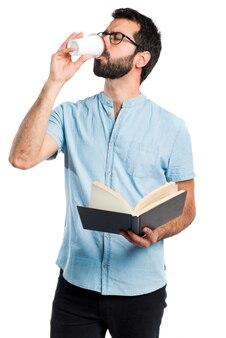 Hombre guapo con gafas azules libro de lectura y beber café
