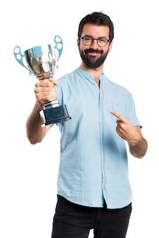 Hombre guapo con gafas azules con un trofeo