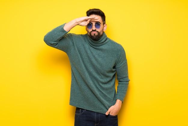 Hombre guapo con gafas de sol mirando de lejos con la mano para mirar algo