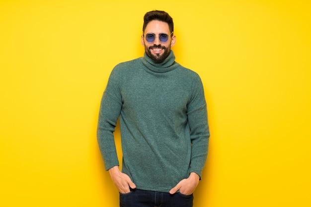 Hombre guapo con gafas de sol posando y riendo mirando al frente
