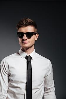 Hombre guapo en gafas de sol y ropa formal posando y mirando a otro lado