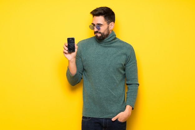 Hombre guapo con gafas de sol con teléfono inteligente roto con problemas