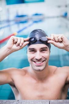 Hombre guapo con gorra de baño y gafas en la piscina