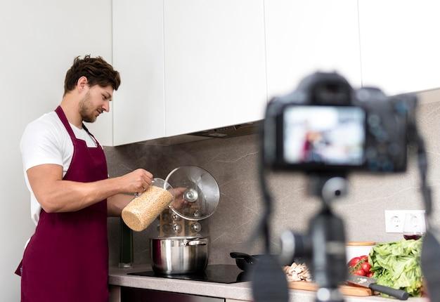 Hombre guapo grabando video de cocina en casa