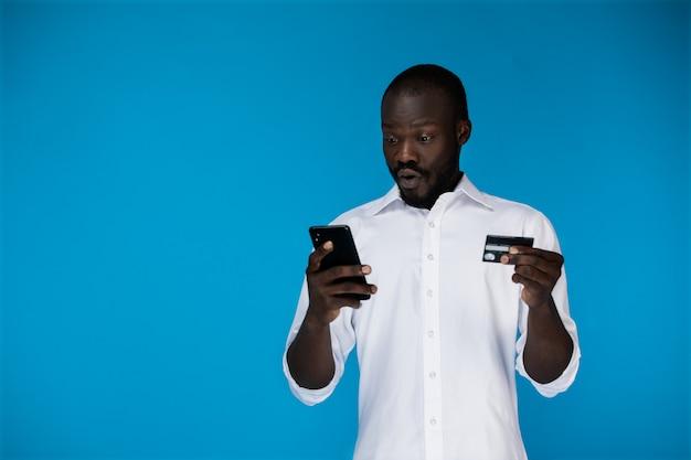 Hombre guapo gratamente sorprendido con una tarjeta de crédito y un teléfono