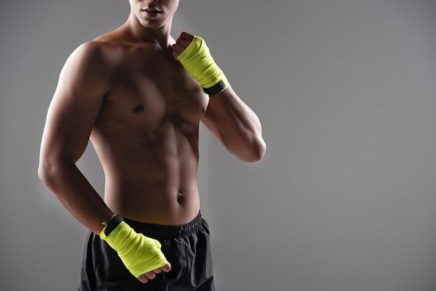 El hombre guapo con guantes amarillos, prepárate para golpear, hacer ejercicio y desarrollar músculos