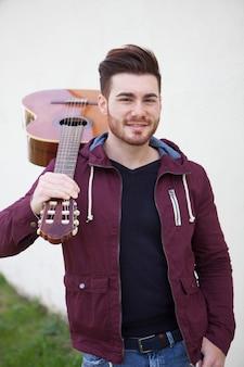 Hombre guapo con una guitarra sobre los hombros