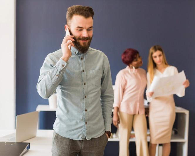 Hombre guapo hablando por teléfono en la oficina