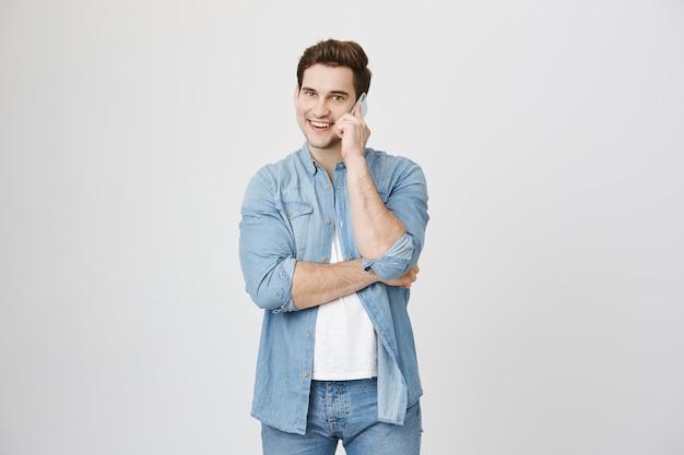 Hombre guapo hablando por teléfono, sonriendo