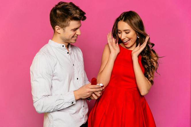 Hombre guapo hace una propuesta a su hermosa novia en vestido rojo con el pelo largo y rizado