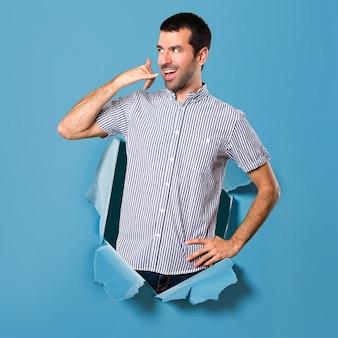 Hombre guapo haciendo gesto de teléfono a través de un agujero de papel