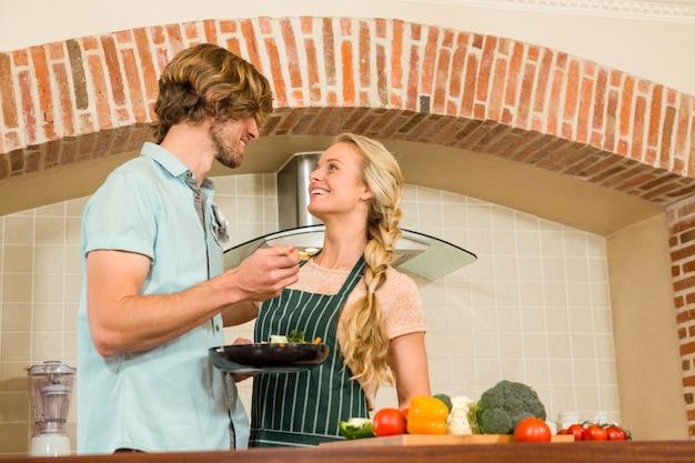 Hombre guapo haciendo que su novia pruebe la preparación en la cocina