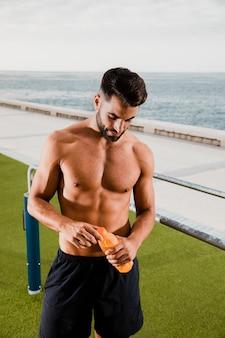 Hombre guapo hidratación después de hacer ejercicio al aire libre