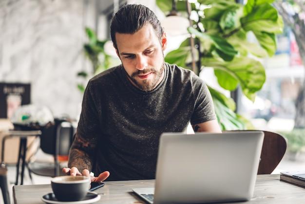 Hombre guapo hipster barbudo uso y mirando la computadora portátil con café