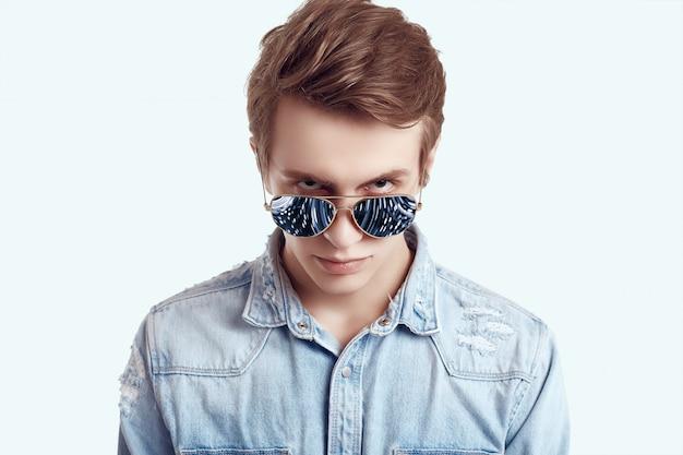Hombre guapo hipster en gafas de sol de moda con chaqueta de jeans