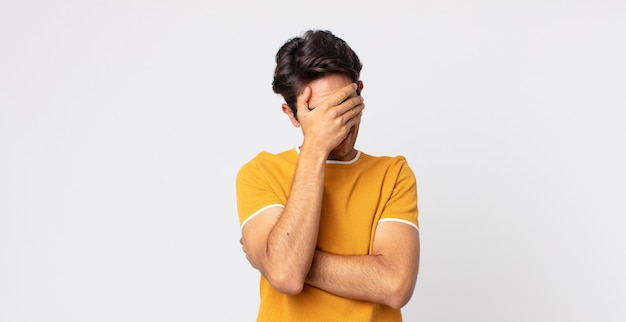 Hombre guapo hispano que parece estresado, avergonzado o molesto, con dolor de cabeza, cubriéndose la cara con la mano