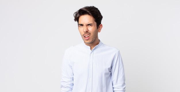 Hombre guapo hispano que se siente desconcertado y confundido, con una expresión muda y atónita mirando algo inesperado