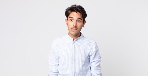 Hombre guapo hispano que se siente desorientado, confundido e inseguro acerca de qué opción elegir, tratando de resolver el problema