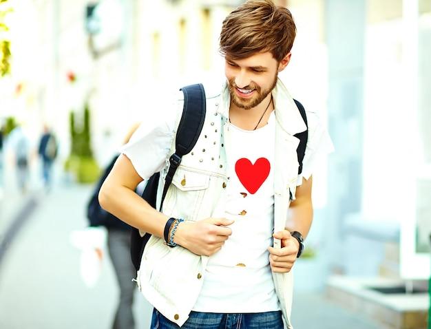 Hombre guapo inconformista sonriente divertido en ropa de verano elegante posando en el fondo de la calle