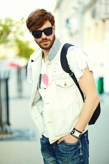 Hombre guapo inconformista sonriente divertido en tela elegante de verano en la calle con gafas de sol