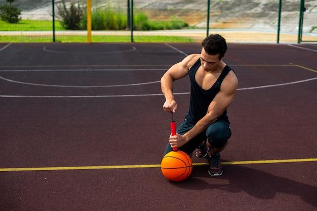 Hombre guapo inflar una pelota bajo ángulo de tiro