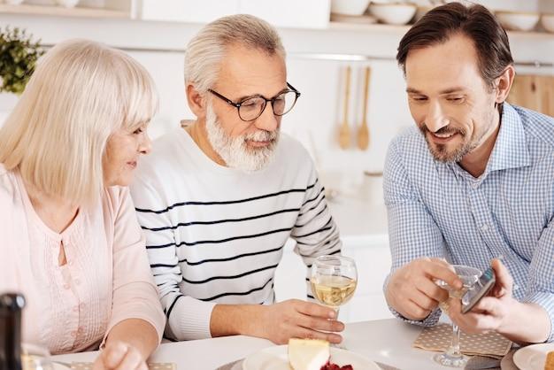 Hombre guapo involucrado feliz cenando y disfrutando del tiempo con sus padres ancianos mientras muestra el teléfono inteligente