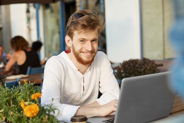 Hombre guapo jengibre adulto con computadora portátil sentado en la terraza de un restaurante o cafetería