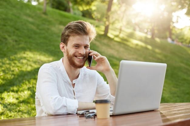 Hombre guapo jengibre maduro con computadora portátil en el parque