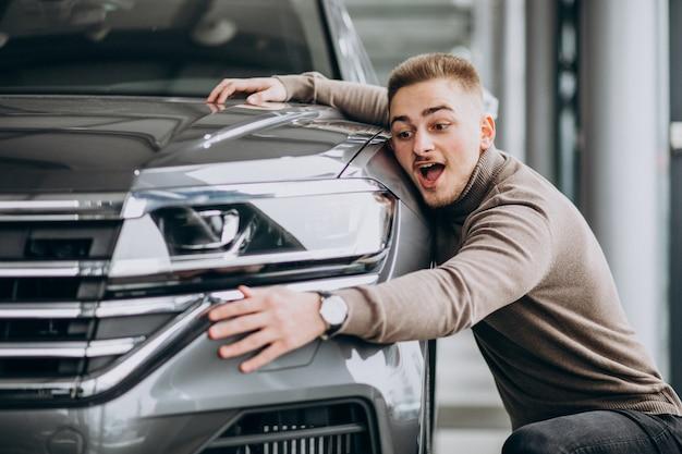 Hombre guapo joven abrazando un coche en una sala de exposición de automóviles