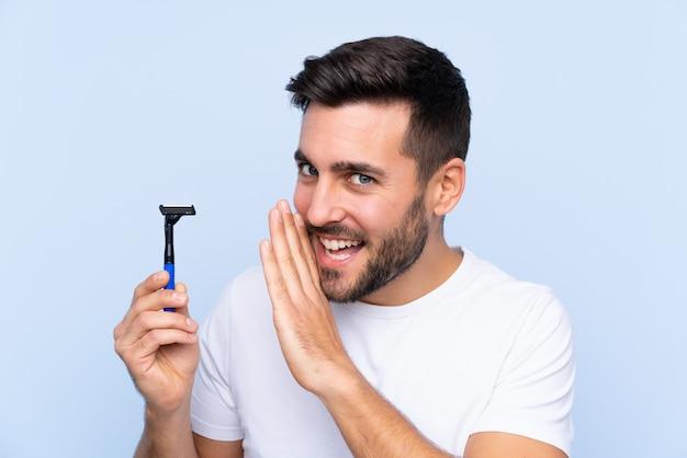 Hombre guapo joven afeitarse la barba susurrando algo