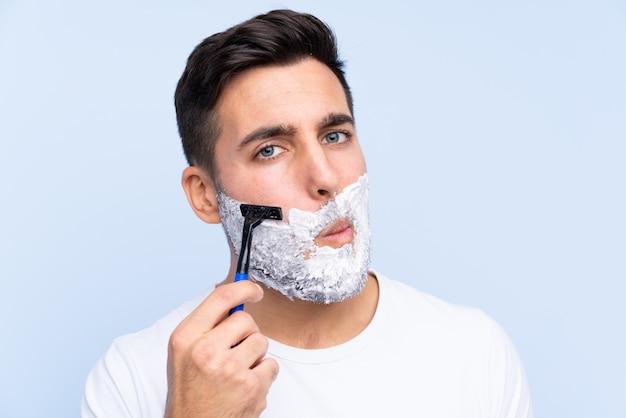 Hombre guapo joven afeitarse la barba