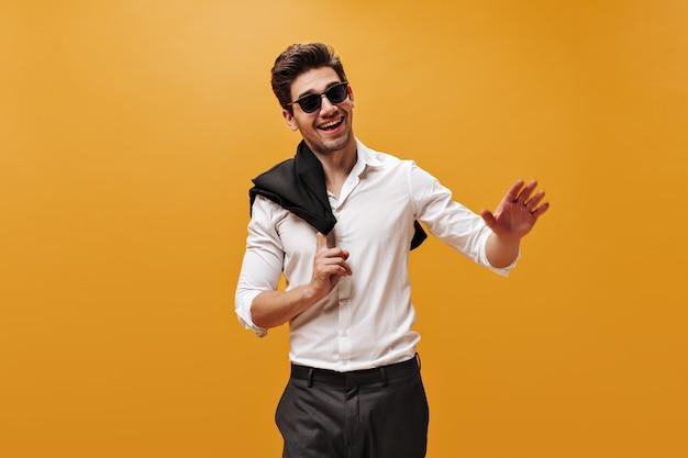 Hombre guapo joven alegre en pantalones, camisa blanca, gafas de sol sonriendo sinceramente y sosteniendo una chaqueta negra en la pared naranja.