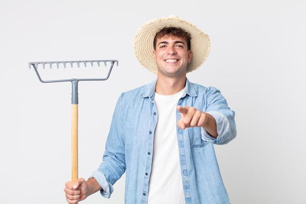 Hombre guapo joven apuntando a la cámara eligiéndote. concepto de granjero