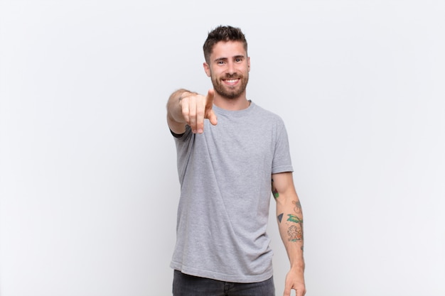 Hombre guapo joven apuntando a la cámara con una sonrisa satisfecha, segura y amigable, eligiéndote contra la pared de color plano