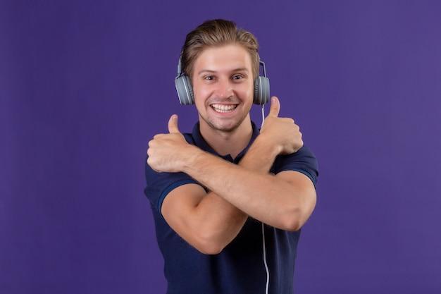 Hombre guapo joven con auriculares de pie con los brazos cruzados mostrando los pulgares arriba sonriendo alegremente sobre fondo púrpura