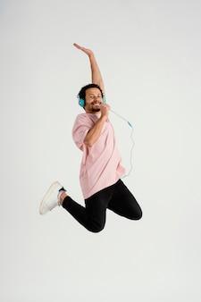 Hombre guapo joven con auriculares saltando Foto Premium