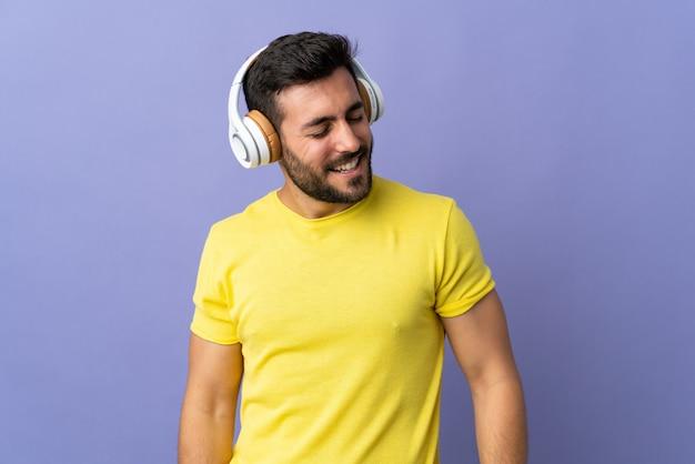 Hombre guapo joven con barba aislado en la pared púrpura escuchando música