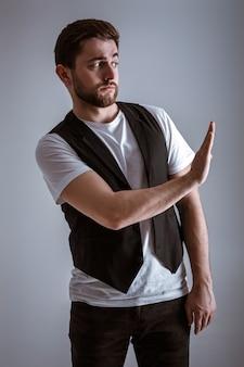Hombre guapo joven con barba con una camisa blanca y un chaleco negro muestra el gesto de parada