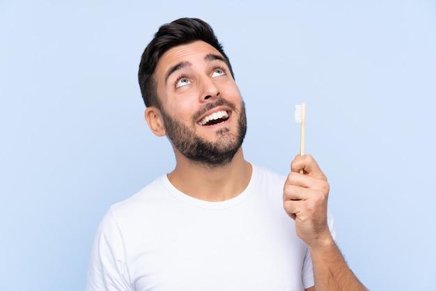 Hombre guapo joven con barba cepillando sus dientes sobre la pared aislada mirando hacia arriba mientras sonríe