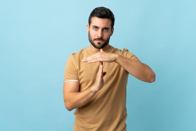Hombre guapo joven con barba sobre pared aislada haciendo gesto de tiempo fuera
