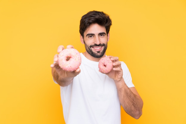 Hombre guapo joven con barba sobre pared amarilla aislada con donas con expresión feliz
