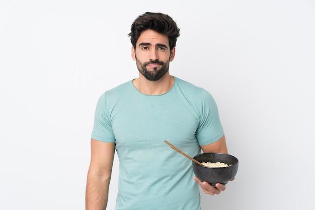 Hombre guapo joven con barba sobre pared blanca aislada con expresión triste mientras sostiene un tazón de fideos con palillos