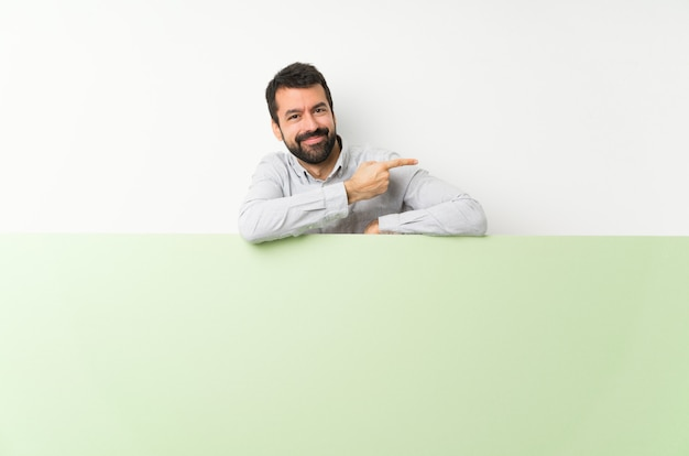 Hombre guapo joven con barba sosteniendo un gran cartel vacío verde señalando con el dedo hacia un lado