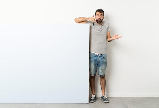 Hombre guapo joven con barba sosteniendo una gran pancarta vacía azul haciendo gesto de teléfono y dudando