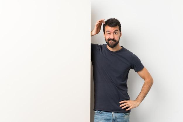 Hombre guapo joven con barba sosteniendo una gran pancarta vacía teniendo dudas mientras se rasca la cabeza