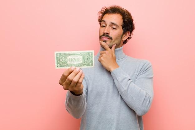 Hombre guapo joven con billetes de dólar contra la pared plana rosa