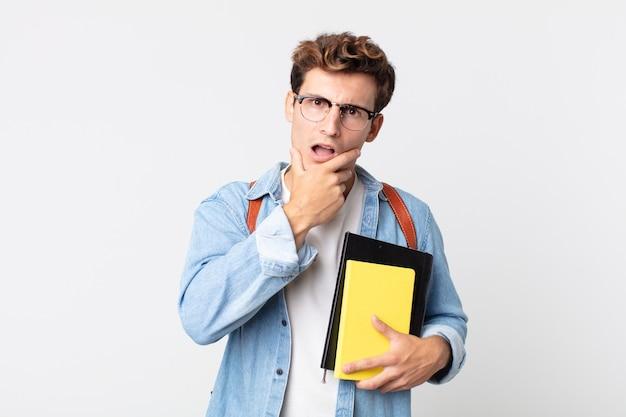 Hombre guapo joven con la boca y los ojos bien abiertos y la mano en la barbilla. concepto de estudiante universitario