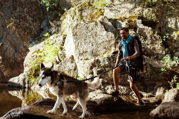 Hombre guapo joven caminando con perros huskies en el cañón cerca del agua