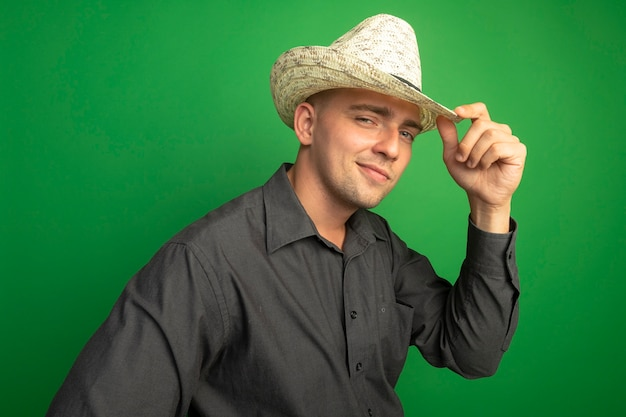 Hombre guapo joven en camisa gris y sombrero de verano mirando confiado tocando su sombrero sonriendo de pie sobre la pared verde