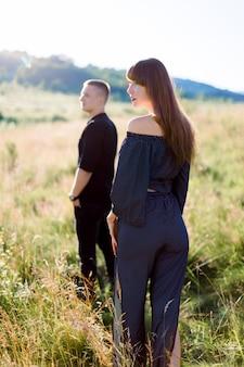 Hombre guapo joven en camisa negra y pantalones esperando a su mujer bonita, de pie en un campo al atardecer de verano